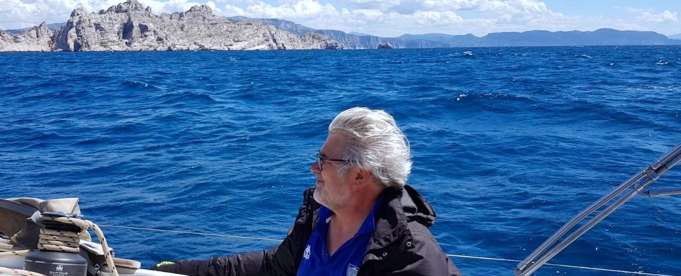 François C. à bord de son Dufour 412 loué chez Filovent en arrière plan l'Île de Riou